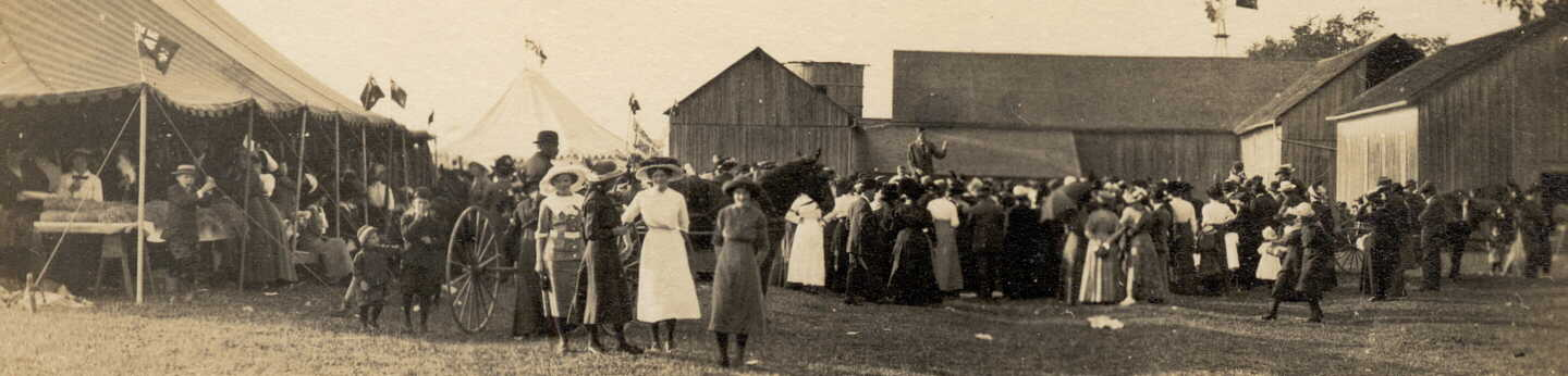 Photograph of people in crowd around fair or circus tent