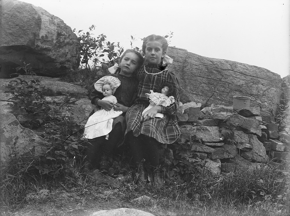 Two girls holding dolls, c.1900
